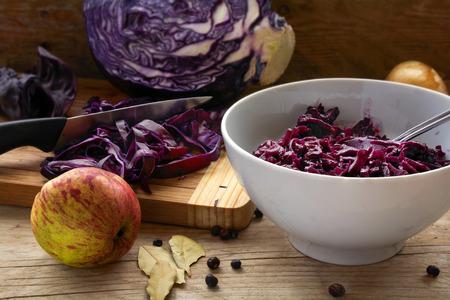 cebolla: preparaci�n de col roja para una cena festiva con manzana, cebolla, hojas de laurel y bayas de enebro en un tablero de madera r�stica, de enfoque seleccionado