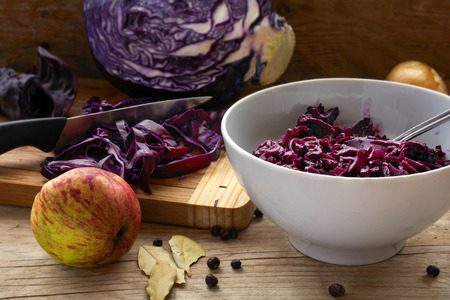 cebolla roja: preparing red cabbage for a festive dinner with apple, onion, bay leaves and juniper berries on a rustic wooden board, selected focus