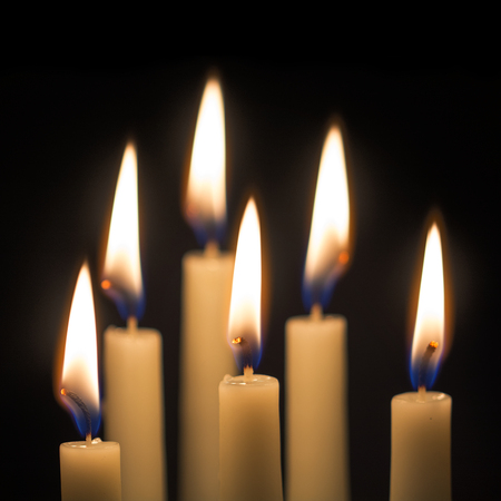 lit candles: group of six burning candles against a black background, selected focus, narrow depth of field