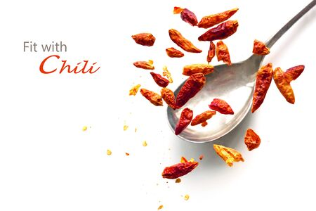 capsaicin: dried chili peppers jumping from a spoon, isolated on a white background, concept for heart health or fat burning with capsaicin, sample text Fit with Chili Stock Photo