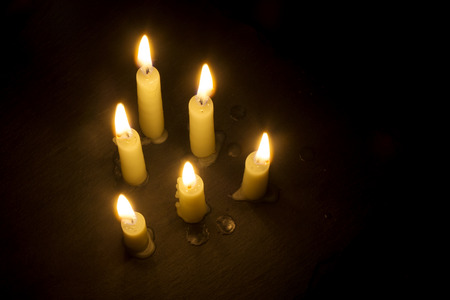surface view: group of six burning candles on a black surface, view from above, generous copy space Stock Photo