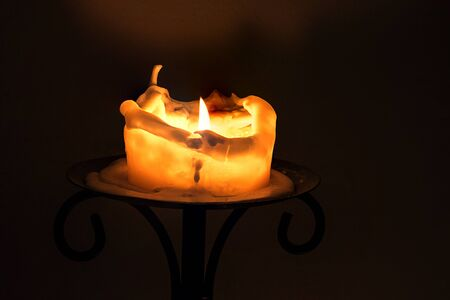 birthday religious: burning big white candle with flame and melting wax on the edge on an iron candlestick against a dark background with copy space Stock Photo
