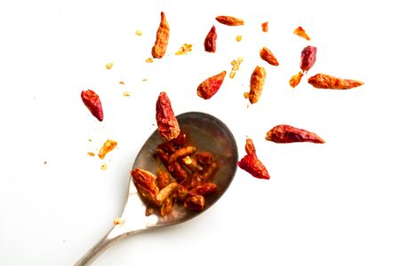 capsaicin: dried chili peppers jumping from a spoon, isolated on a white background, concept capsaicin for heart health, muscle pain, inflammation or fat burning