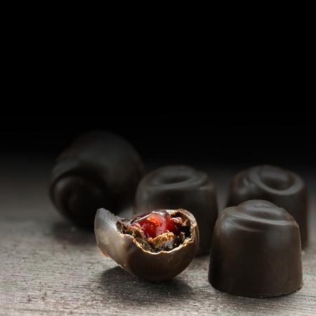 bombones de chocolate fino con relleno de mermelada de frutos rojos en una mesa de madera rústica, se desvanecieron fondo oscuro a negro, copia espacio generoso, primer shotwith enfoque seleccionada y la profundidad del campo estrecha