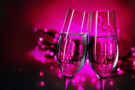 clink: Two champagne flutes clink glasses on New Years party, purple background with blurred lights and copy space