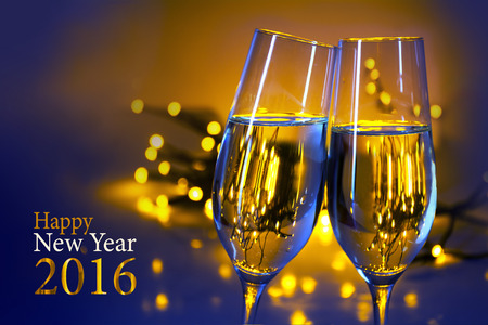 Two champagne flutes clink glasses at the party, blue yellow background with blurred golden lights and text Happy New Year 2016