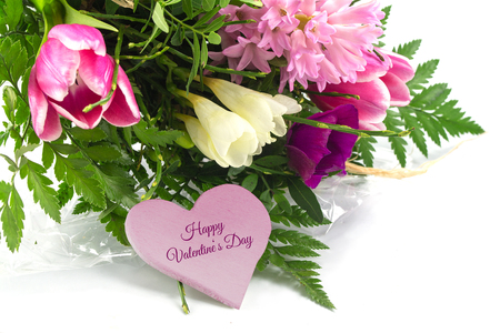 bouquet of spring flowers in the corner and a pink heart shape with text happy valentiners day, isolated with shadows on a white background, selected focus