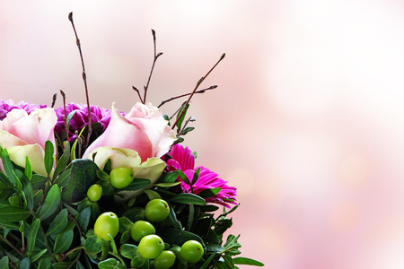 Bouquet with bright pink roses in the corner against a blurred pink background with copy space