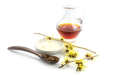 bloeiende toverhazelaar (Hamamelis), gedroogde bladeren, room en de essentie voor zelfgemaakte huidverzorging cosmetica en badadditief, geïsoleerd met schaduw op een witte achtergrond