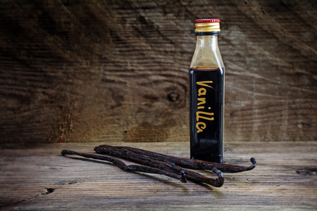 vanilla extract, homemade in a small bottle and vanilla beans on a rustic wooden background