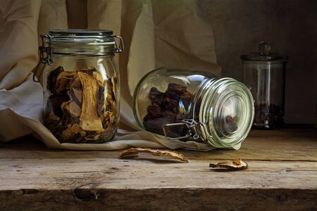 glass jars: glass jars with dried tomatoes and mushrooms on an old wooden shelf in the rustic storage chamber, countryside still life