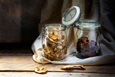 larder: glass jars with dried tomatoes and mushrooms on an old wooden shelf in the rustic storage chamber, countryside still life, copy space in the dark background Stock Photo
