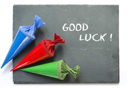 three colurful school cones on a blank blackboard, message good luck, isolated on a white background