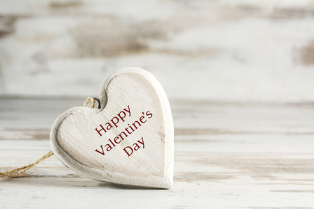 narrow depth of field: white vintage heart of wood against a white painted wooden background, love concept with text Happy Valentines Day, closeup with selected focus and narrow depth of field