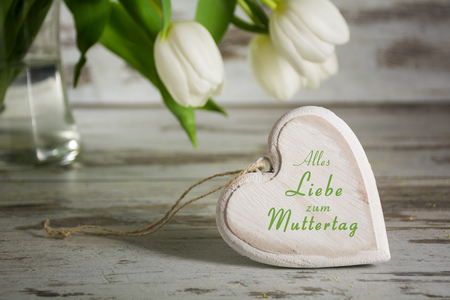 all love: heart shape of wood in front of white tulips on a gray  rustic wooden table, german text Alles Liebe zum Muttertag, that means All Love to your Mothers Day, closeup with selected focus and narrow depth of field