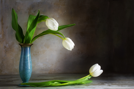 longing: longing for light, vintage still life with white tulips and a blue porcelain vase on an old wooden table against a rustic wall, copy space Stock Photo
