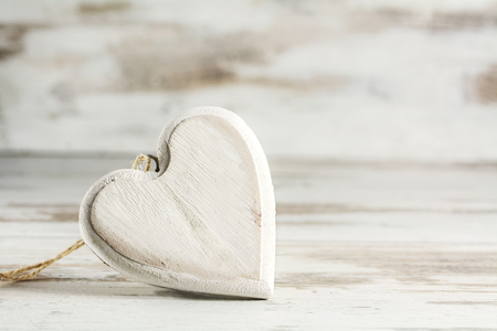 narrow depth of field: free standing vintage heart of wood against a white painted wooden background, love concept with copy space, closeup with selected focus and narrow depth of field Stock Photo