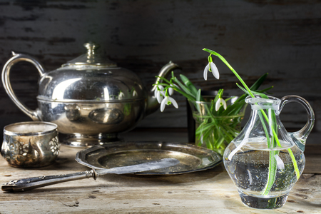 narrow depth of field: morning with snowdrops and silver breakfast dishes, teapot, plate and knife on a rustic wooden table, still life with selected focus and narrow depth of field