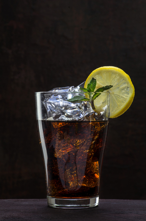 glass of cola or coke with ice cubes, lemon slice and peppermint garnish on a wooden table against a dark brown wall, copy space, selected focus, vertical