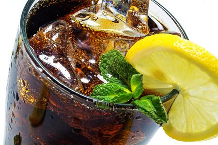 bovenkant van een glas cola of cola met ijsblokjes, citroen segment en pepermunt garneren, close-up met geselecteerde focus en smalle diepte van het veld Stockfoto