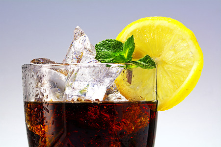 top of a glass of cola or coke with ice cubes, lemon slice and peppermint garnish, closeup with selected focus