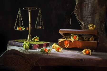 life metaphor: physalis fruits escape from a jewelery box to a brass scale, still life metaphor in painting style on a rustic wooden table in front of a dark vintage wall,  concept, worth of freedom against money