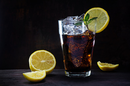glass of cola or ice tea with ice cubes, lemon slices and peppermint garnish on a wooden table against a dark brown wall, copy space, selected focus