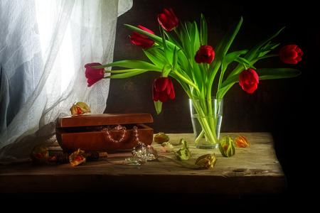 bouquet of red tulips, jewelery box with necklace and some physalis, still life in painting style on a rustic wooden table in front of a white curtain and a dark vintage wall, soft focus Фото со стока