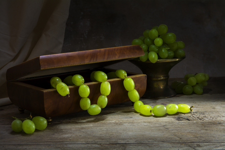 life metaphor: green grapes hanging like a necklace from a jewelery box on a rustic wooden table, still life metaphor concept, nutrition is the treasure of our health Stock Photo