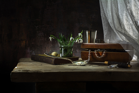 still life with jewelery box, necklace, old book, snowdrop flowers and white curtain on a rustic wooden table in front of a dark vintage wall, copy space Фото со стока