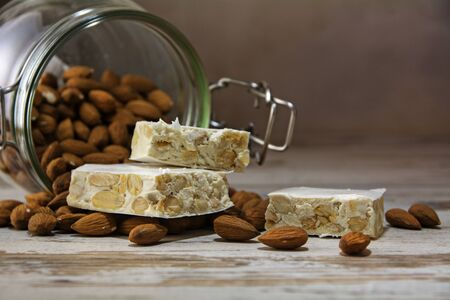 mediterranean festive torrone or nougat in front of a glass jar with almonds on a rustic wooden table, copy space, close up with selected focus and very narrow depth of field 版權商用圖片