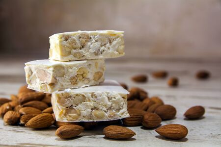 Italian festive torrone or nougat and almonds on a rustic wooden table, copy space, close up with selected focus, very narrow depth of field 版權商用圖片
