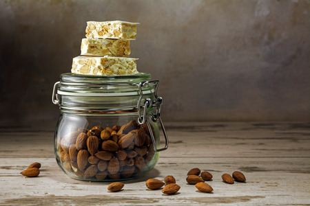 narrow depth of field: mediterranean festive torrone or nougat on a glass jar with almonds on a rustic woodn table, copy space, selected focus, narrow depth of field Stock Photo