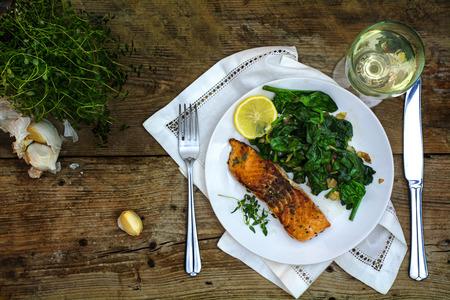 サーモンのグリル、タイム、レモン、白い皿にほうれん草と暗い素朴な木製のテーブル、上から地中海の菜食主義者の低炭水化物料理観トップ白ワ