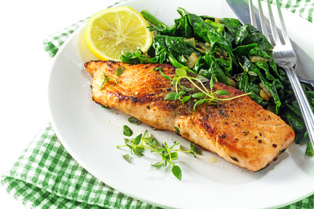 grilled salmon with thyme, lemon and spinach on a plate, vegetarian low carb dish, green white napkin on a white background, selected focus, narrow depth of field