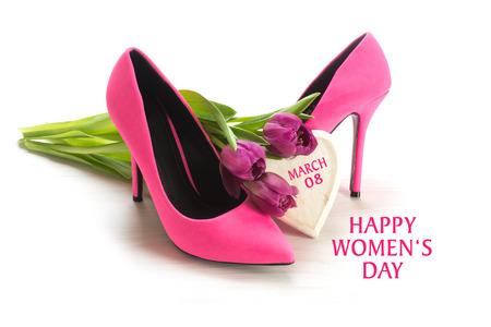 Internationale Vrouwendag 8 maart wenskaart met dames roze schoenen met hoge hakken, tulpen en een houten hart, geïsoleerd met schaduwen op een witte achtergrond, voorbeeld tekst
