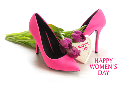 International Women's Day 8 March, greeting card with ladies pink high heel shoes, tulips and a wooden heart, isolated with shadows on a white background, sample text