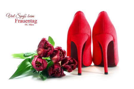Ladies red high heel shoes from behind and tulips isolated with shadows on a white background, concept symbol for love, german sample text Viel Spaß beim Frauentag (Happy Women's Day) March 08, selected focus