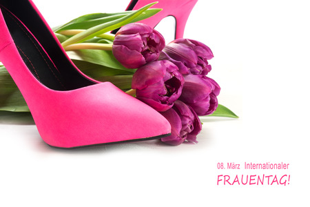 International Womens Day 8 March in german text Internationaler Frauentag, with ladies pink high heel shoes and tulips, corner background isolated with shadows on white Stock Photo