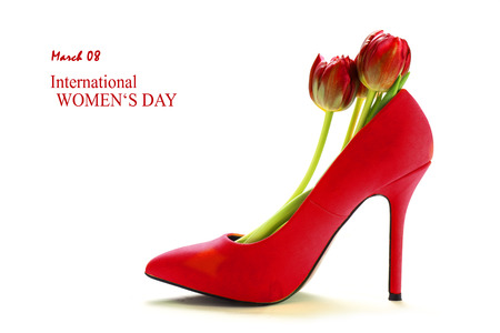 Ladies red high heel shoe in profile with tulips inside, isolated with shadows on a white background, sample text March 08 International Womens Day Foto de archivo