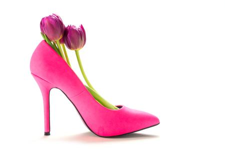 Ladies roze hoge hak schoen in profiel met tulpen binnen, geïsoleerd met schaduwen op een witte achtergrond, concept voor vrouw, liefde, valentijnskaarten en vrouwen dag Stockfoto