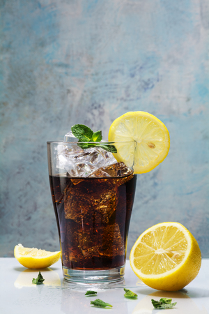 coke: glass of cola or coke with ice cubes, lemon slices and peppermint garnish against a blue vintage wall,  copy space, selected focus Stock Photo