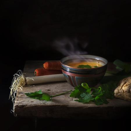 stomend hete groentesoep met peterselie garnituur in een klei kom en ingrediënten op een oude rustieke houten tafel tegen een donkere achtergrond met royale kopie ruimte