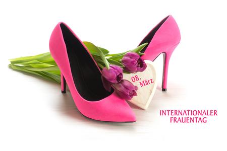 Internationale Vrouwendag 8 maart duits tekst Internationaler Frauentag, wenskaart met dames roze schoenen met hoge hakken, tulpen en een houten hart, geïsoleerd met schaduwen op een witte achtergrond Stockfoto