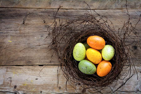top veiw: easter eggs green and orange in a nest on rustic wooden planks with copy space, view from above Stock Photo