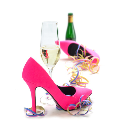 womens day party, ladies pink high heels shoes, streamers, champagne glass and bottle, isolated on a white background, selected focus, narrow depth of field
