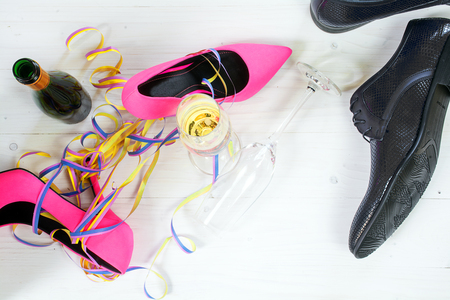 ladies pink high heel stilettos and black mens shoes lying on the floor between champagne and streamers, concept for a wild party, top view from above