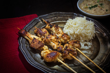 narrow depth of field: Asian meat skewers with rice and satay peanut sauce on a silver plate, red serviette, dark background, selected focus, narrow depth field