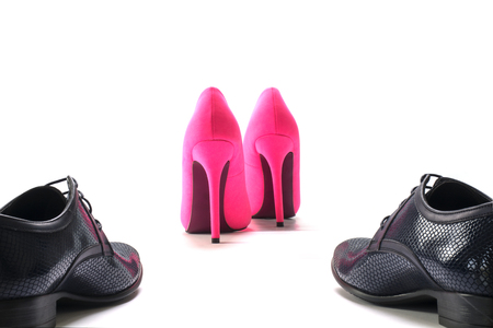 dominance: black mens shoes pursue ladies pink high heels from behind, concept of gender issues as diversity, separation, domination and conflict, isolated with shadows on a white background, selected focus