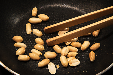 satay sauce: Peeled peanuts roasted in a black pan as a snack or to cook Asian satay sauce, selected focus, narrow depth of field Stock Photo